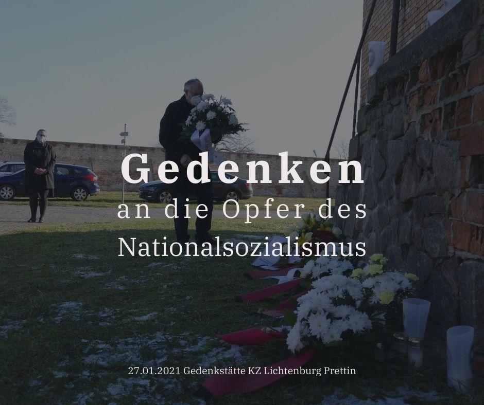 Der Bürgermeister legt ein Gesteck zum Gedenken der Opfer des Nationalsozialismus an der Zellenwand der Lichtenburg nieder